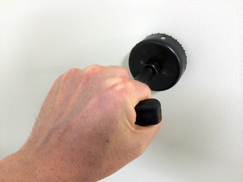 Cut the grommet hole by hand is easy with the included hole saw. Or remove the handle and attach it to your drill.
